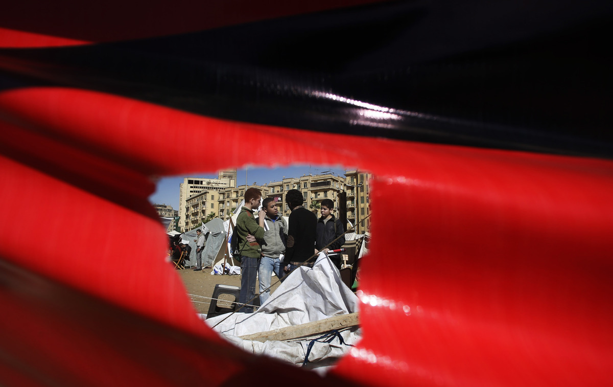 Egyptian boys, seen through a hole in a poster, talk near their tent at the Tahrir Square in Cairo, Egypt, Monday, Dec. 10, 2
