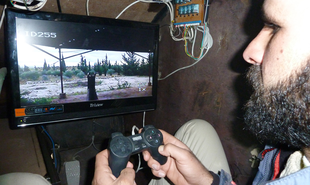 A Syrian rebel uses a control stick to activate the machinegun of Sham II, a homemade armoured vehicle made by the rebels' Al