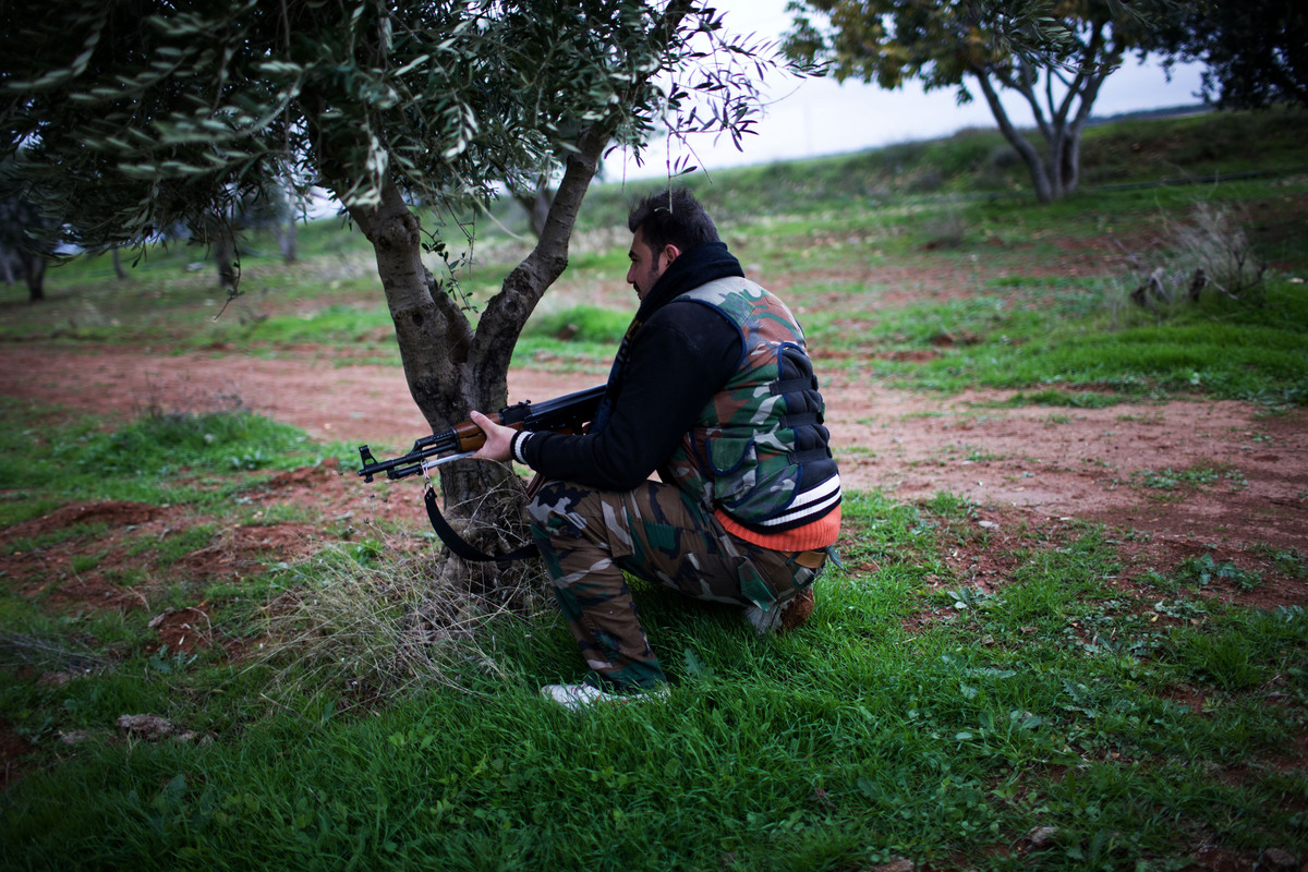 A Free Syrian Army fighter holds his weapon as he prepares himself for advance, close to a military base, near Azaz, Syria, M