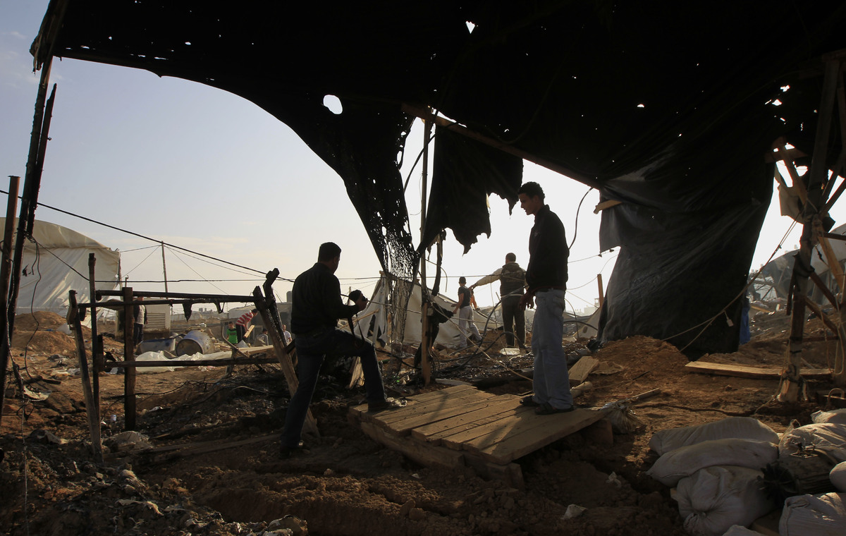 Palestinians inspect destroyed tents near bombed smuggling tunnels between the southern Gaza Strip and Egypt in the border to