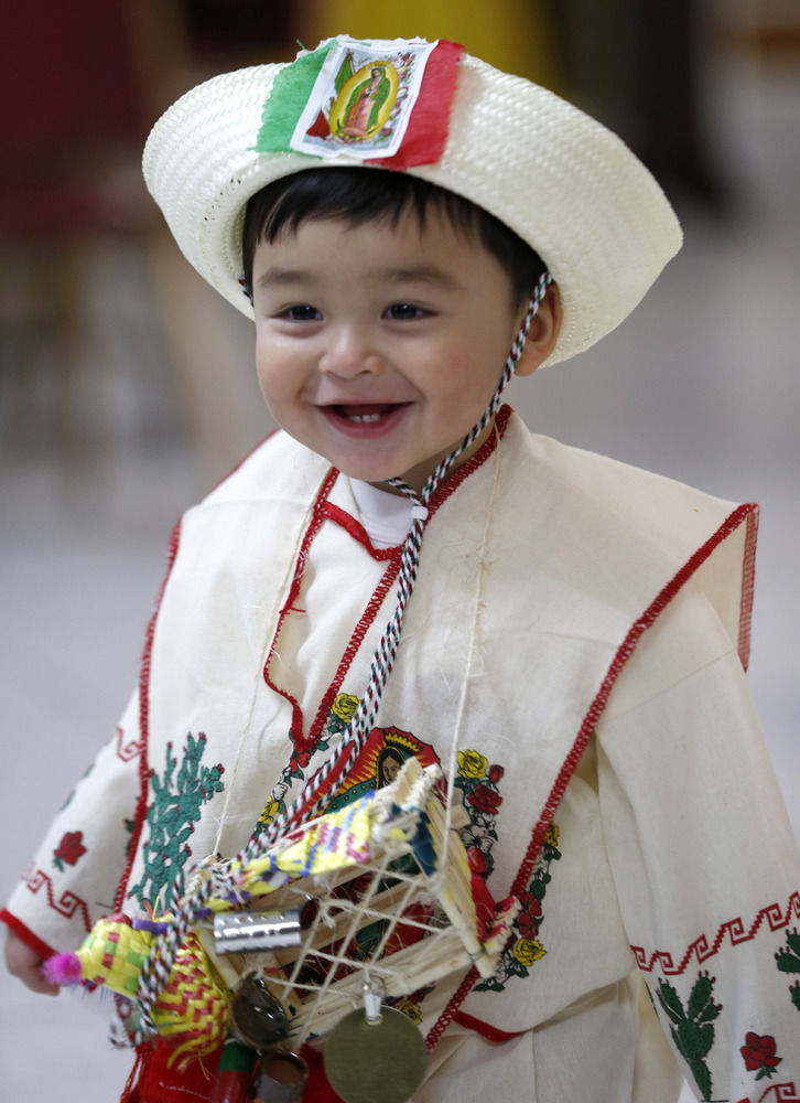 Joseph Villanueva, 18-months, is dressed in Mexican indigenous clothing during a celebration of Virgin of Guadalupe's feast d
