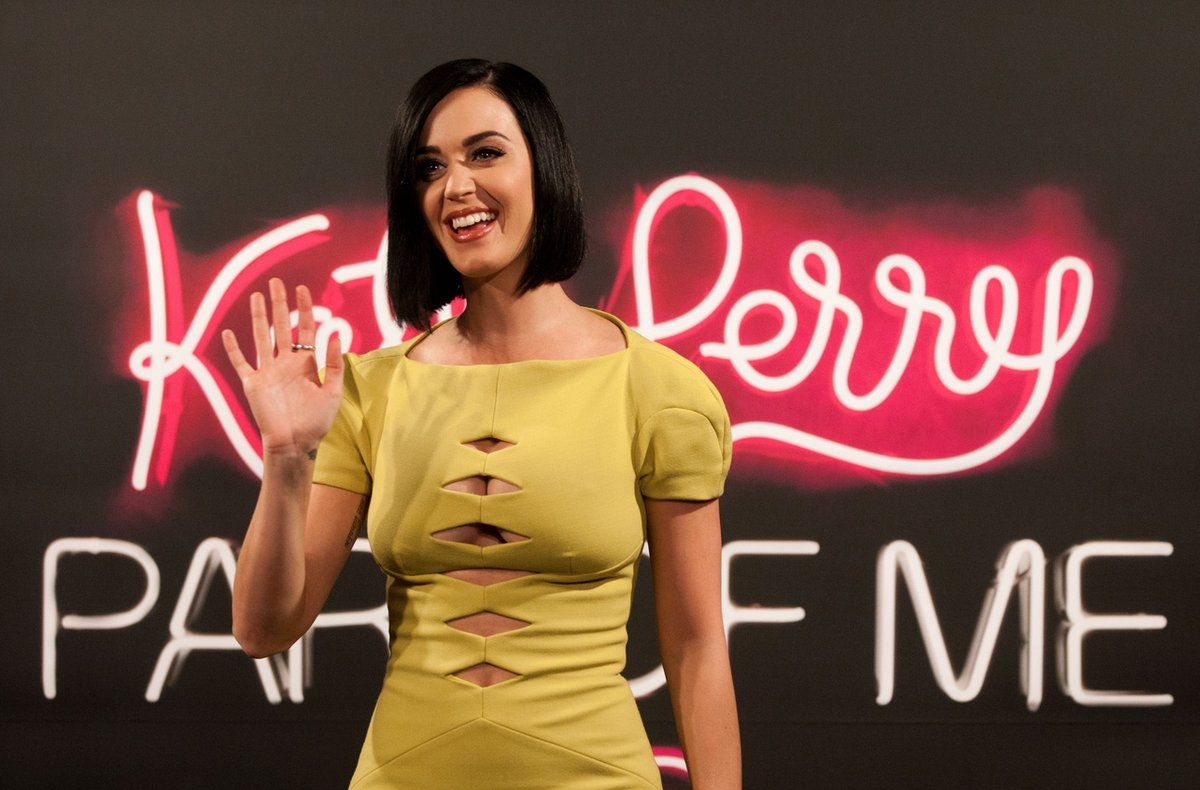 """U.S. singer and actress Katy Perry waves as she poses for photos during a photo call to promote her movie """"Part of me 3D"""" in"""