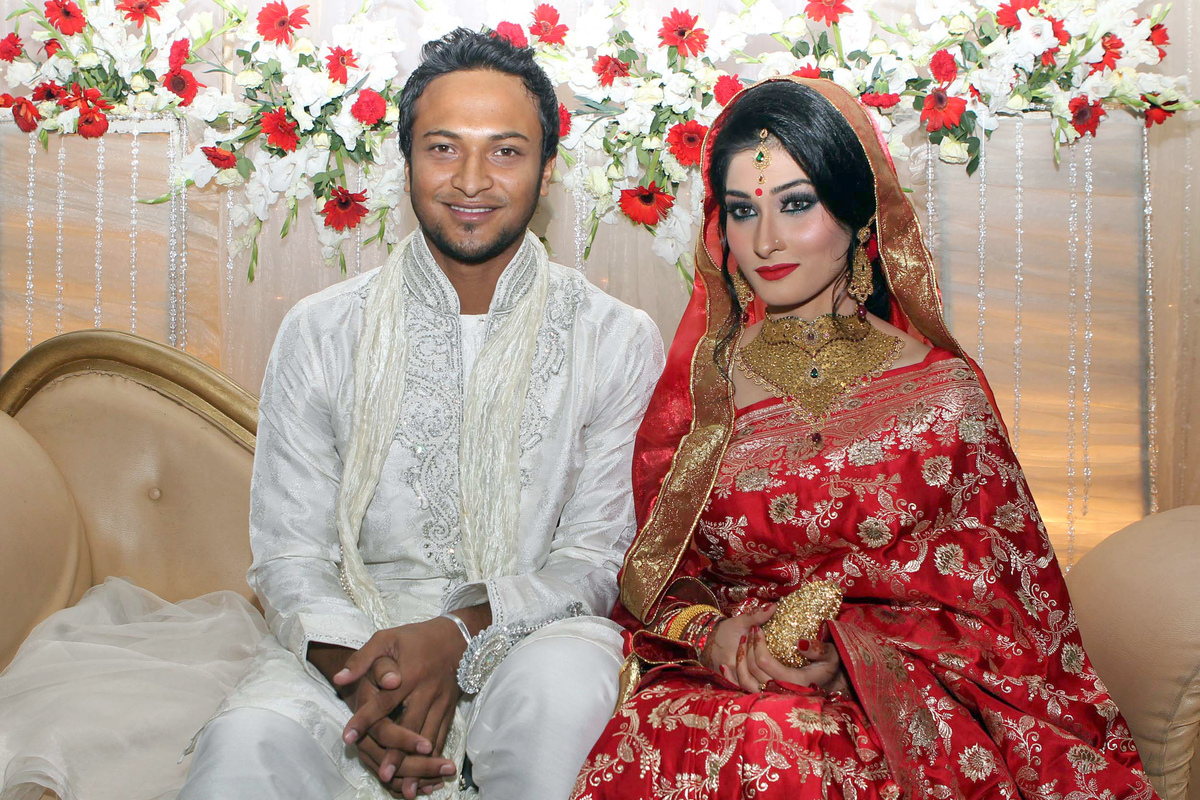 Bangladesh cricket player Shakib al Hasan (L) and his wife Umme Ahmed Shishir pose for a photo during their wedding ceremony