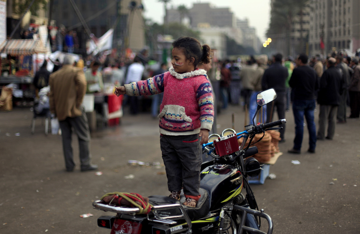 An Egyptian girl wears national flag colors painted on her face as she stands on her father's motorcycle during a demonstrati