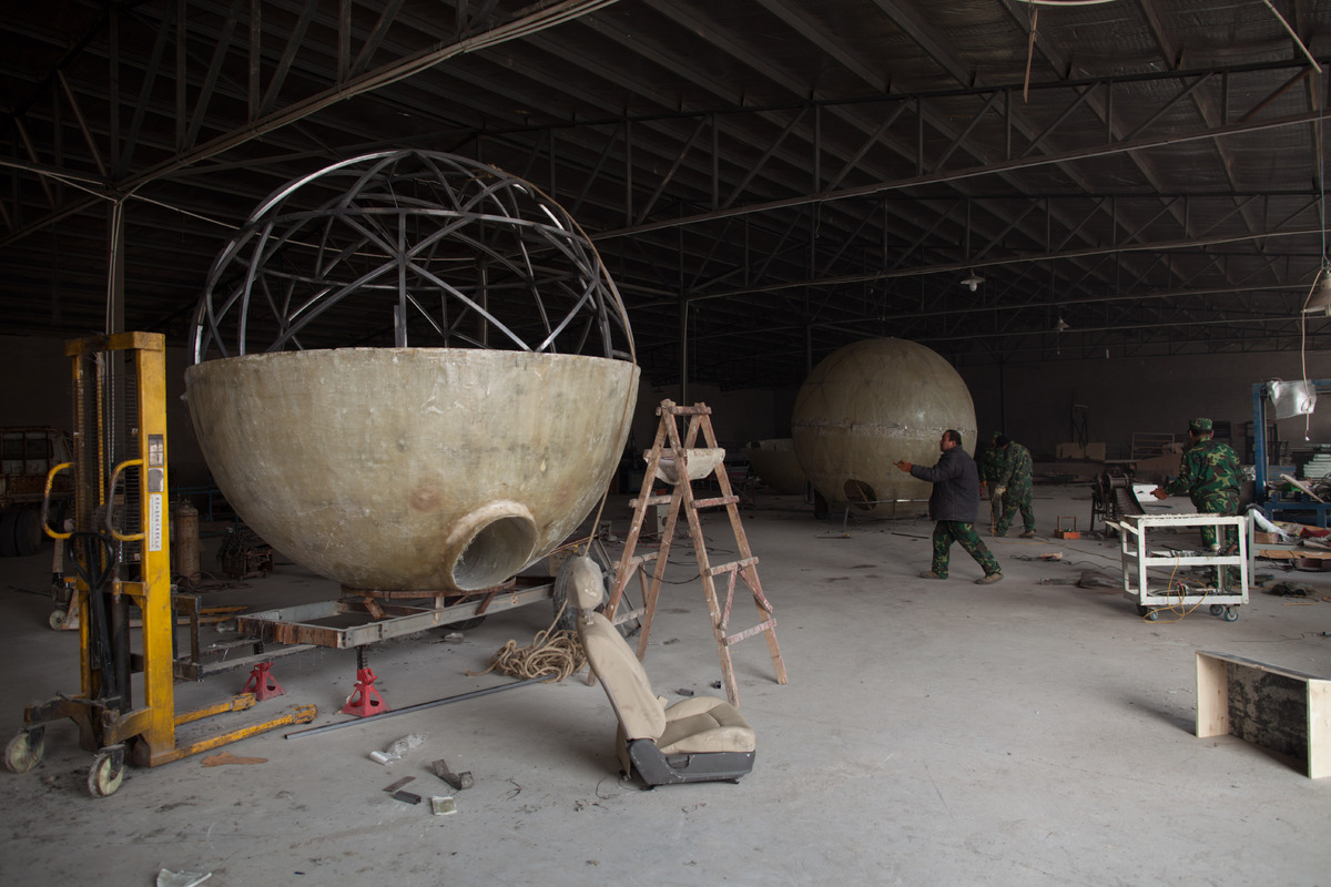 Incomplete survival pods stand in the workshop of farmer Liu Qiyuan which he has also dubbed 'Noah's Arc', in a yard at his h