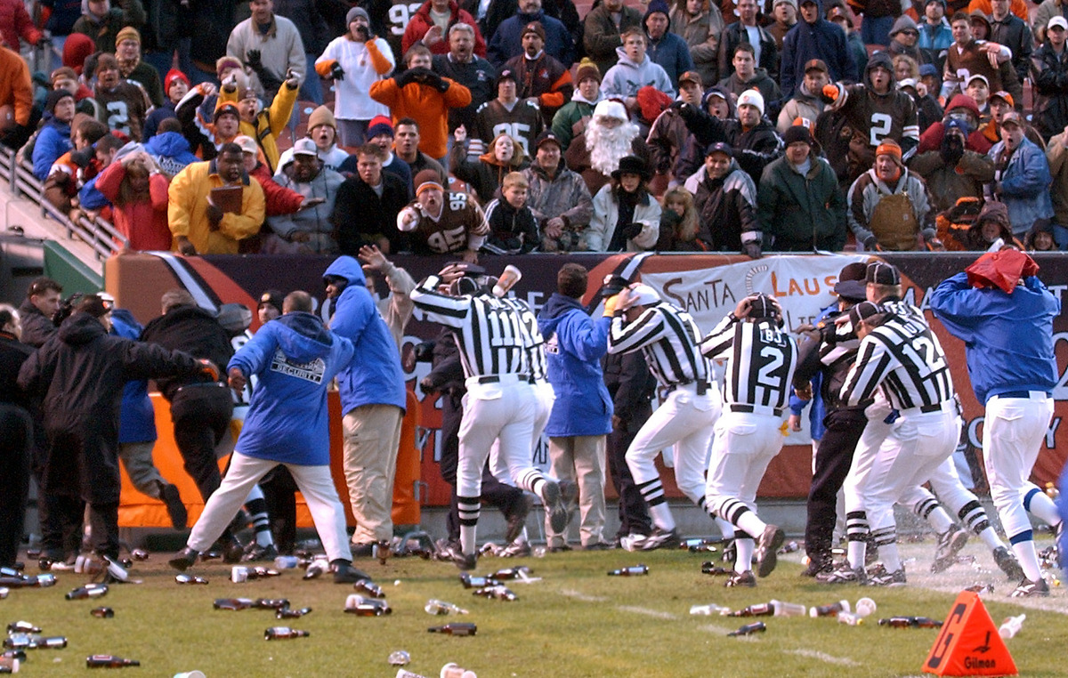 In this Dec. 16, 2001, file photo, officials cover their heads as they leave the field amid debris thrown by fans after an NF