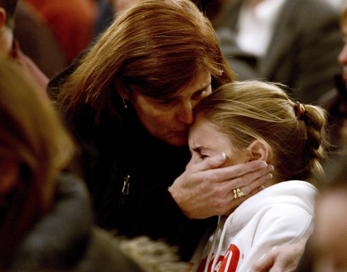 A woman comforts a young girl during a vigil service for victims of the Sandy Hook Elementary shooting, Friday, Dec. 14, 2012