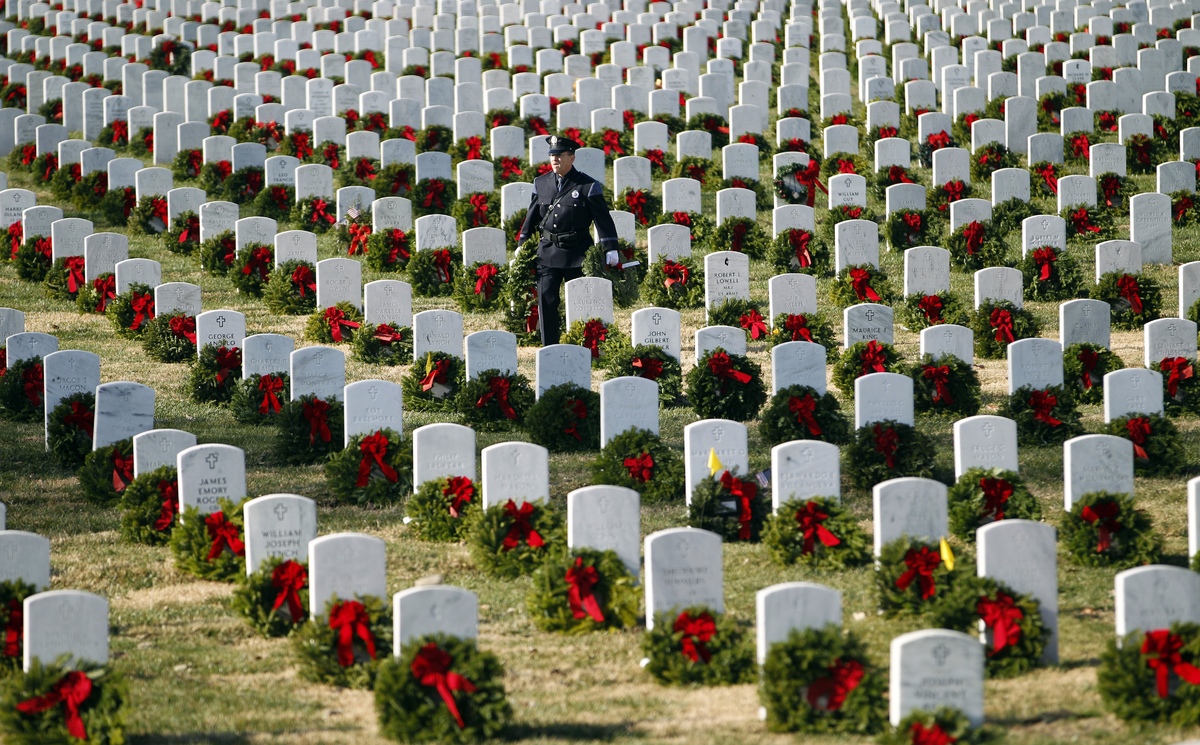 Police officer Terry Fitzgerald of Portland, Maine, carries wreaths as he helps lay holiday wreaths at graves at Arlington Na