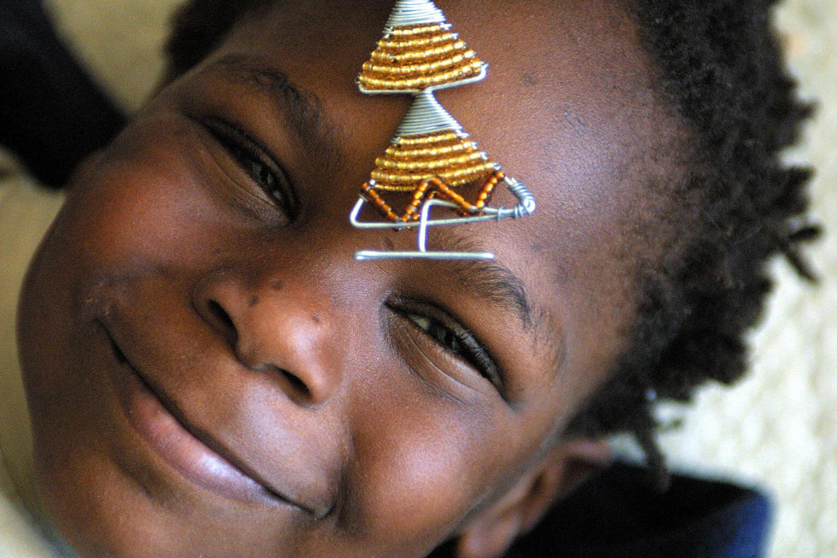 Geseënde Kersfees. Pronounced: GHUH-SAY-UHN-DUH KERS-FACE   <em>Caption: Five year old Vuyani takes time out from decorating