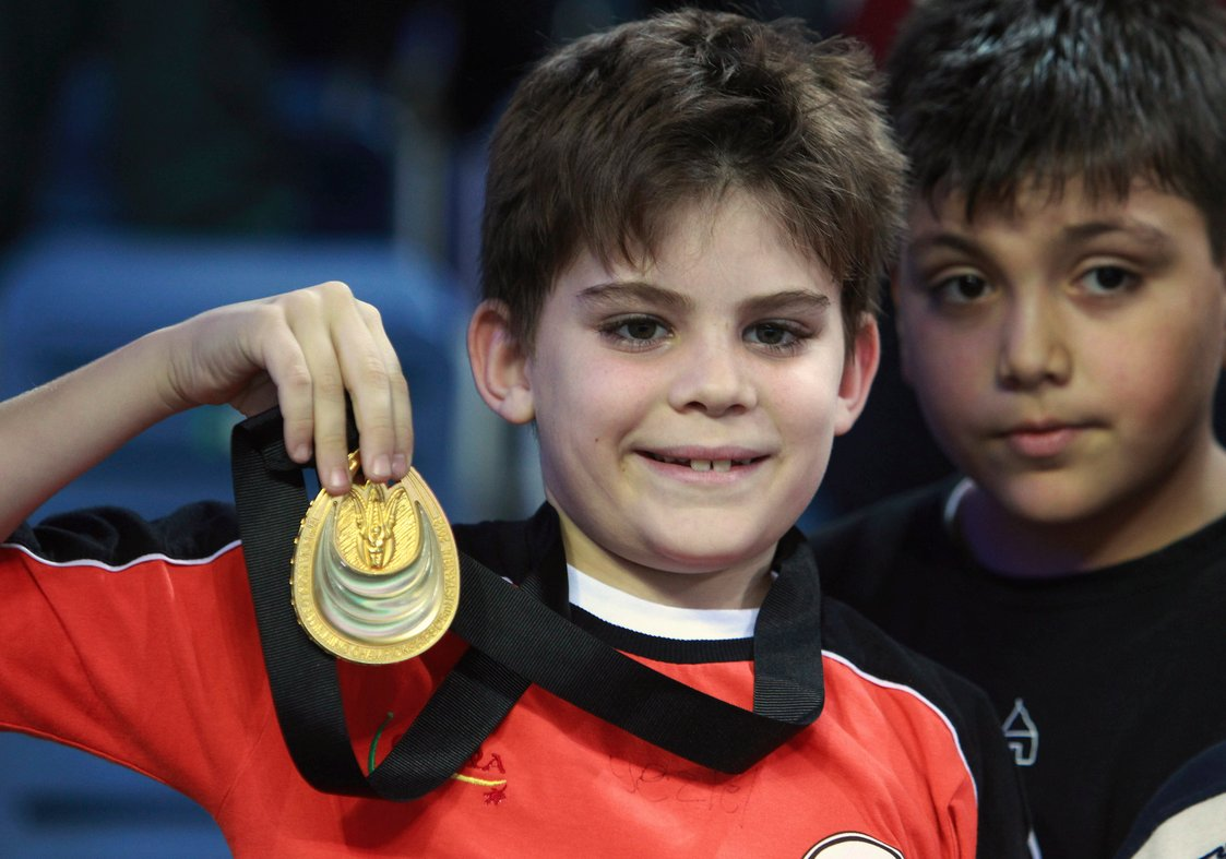 Arda poses for the camera after receiving the gold medal from Ryan Lochte
