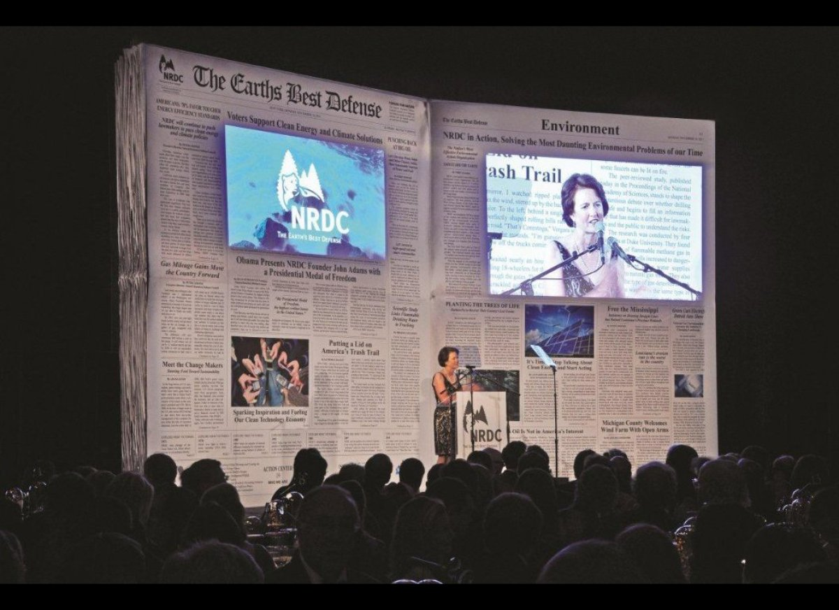 """A giant facsimile of a newspaper is the stage backdrop of a recent NRDC gala, the"""" paper's"""" headlines heralding the organizat"""