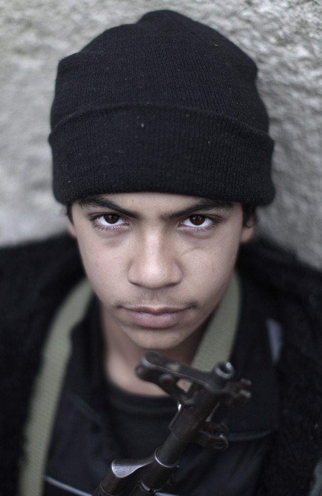 In this Monday, Dec. 17, 2012, photo, Syrian rebel fighter, Abbas Awsara, 16, a former student, poses for a picture, followin