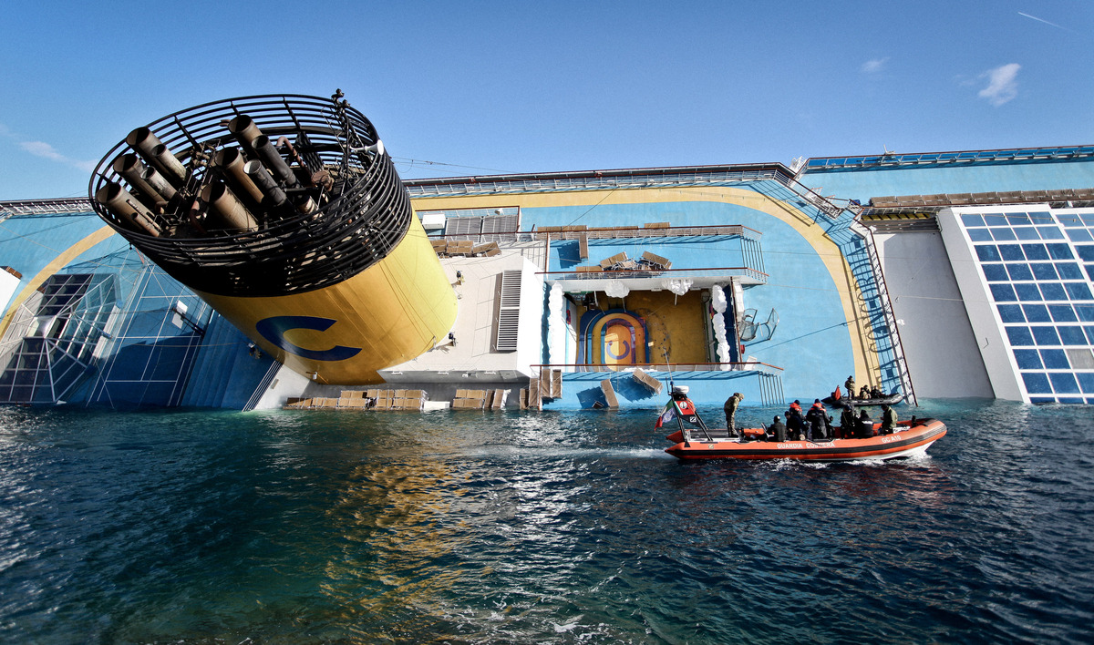 The cruise ship Costa Concordia lies half submerged on its starboard side two days after hitting a rock off the coast of Gigl