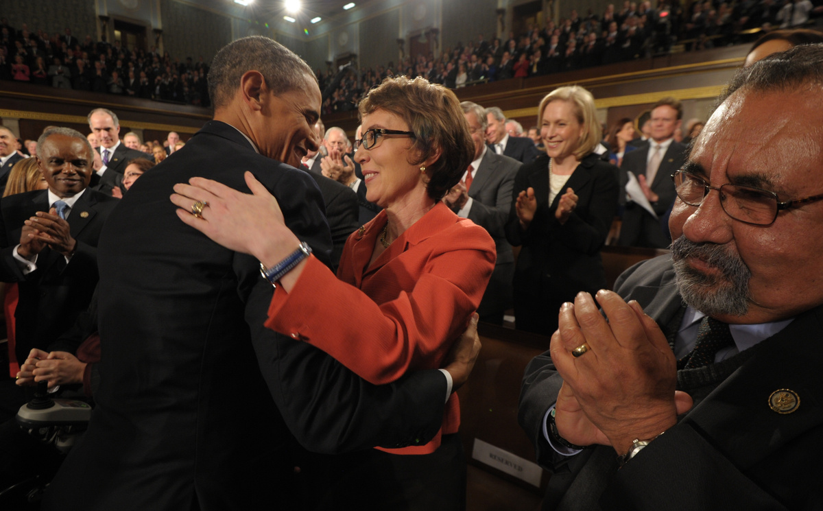 President Obama warmly embraces Rep. Gabrielle Giffords as members of Congress applaud, before he takes the states for his ad
