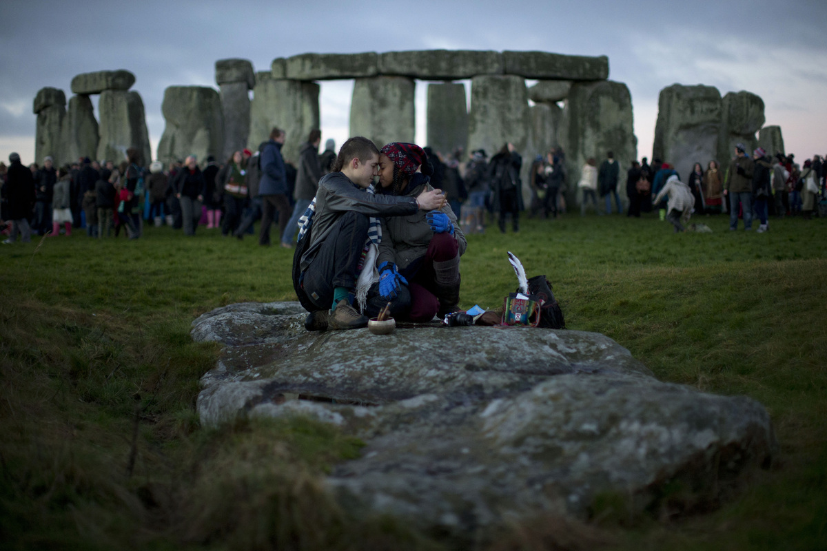 People embrace by the ancient stone circle of Stonehenge, in southern England, as access to the site is given to druids, New
