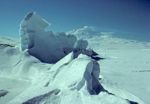 Pressure ridges form where seasonal ice pushes against the shore of Ross Island. Rising to a height of 12,450 feet, Mt. Erebu