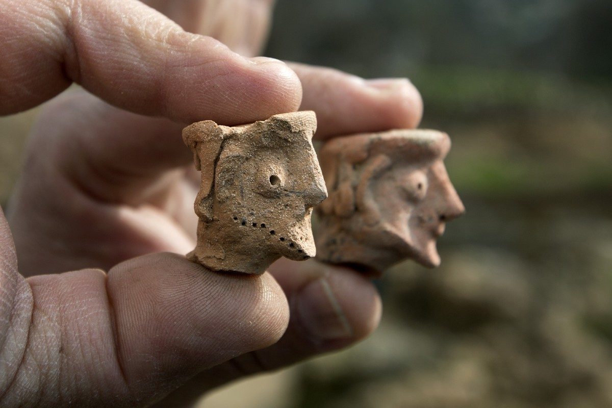 An Israel Antiquities Authority archeologist displays on December 26, 2012 clay figurines used for religious rituals and prac