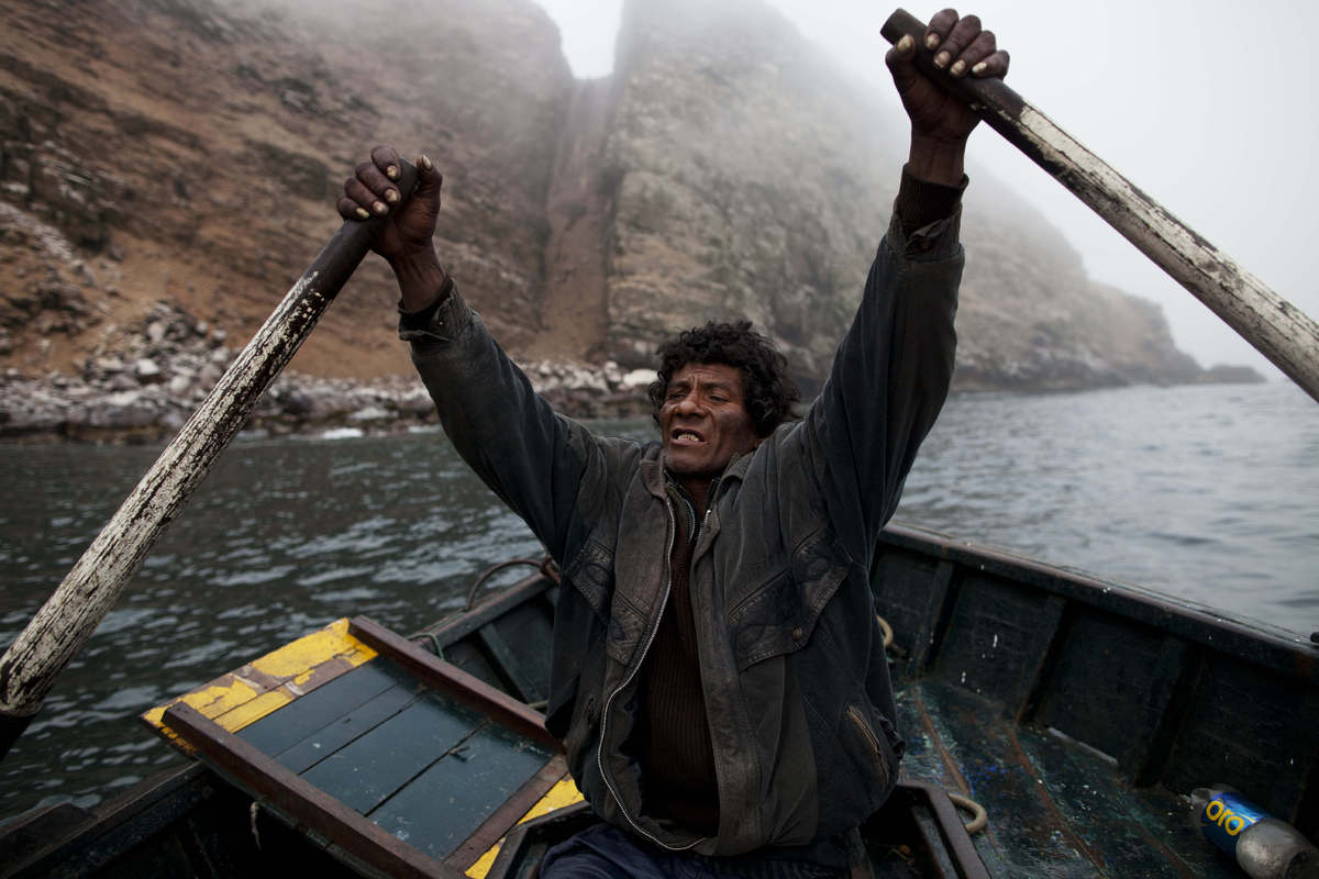 In this Dec. 1, 2012 photo, fisherman Alvaro rows a small boat during a fishing expedition in the Pacific Ocean, off the coas