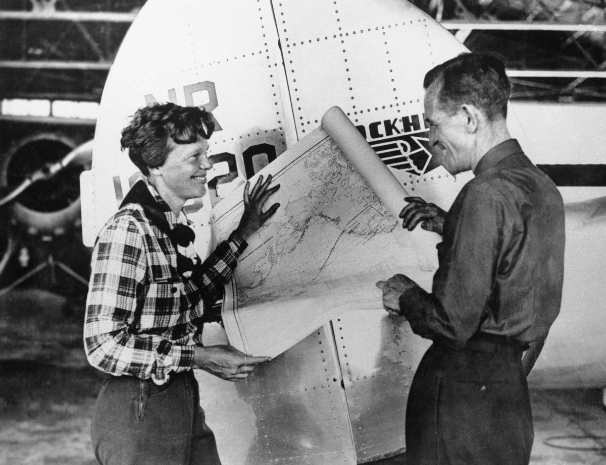 FILE - In this undated photo, Amelia Earhart, left, and navigator Fred Noonan pose with a map of the Pacific showing route of