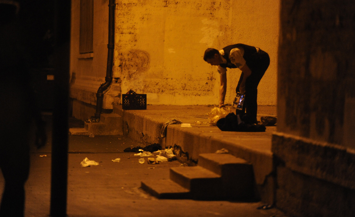 A Chicago police officer picks through debris at the crime scene early Friday, Sept. 20, 2013, where a number of people, incl