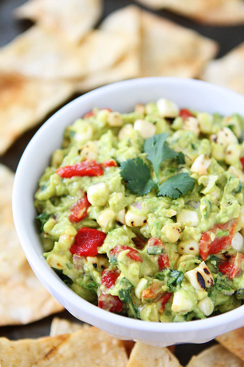 "<strong>Get the <a href=""http://www.twopeasandtheirpod.com/roasted-corn-red-pepper-guacamole/"" target=""_blank"">Roasted Corn &"
