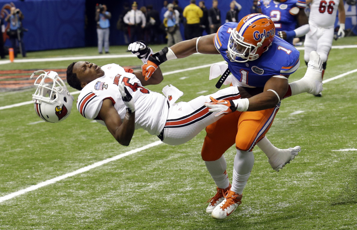 Florida linebacker Jon Bostic (1) hits Louisville quarterback Teddy Bridgewater (5) hard enough to dislodge his helmet in the