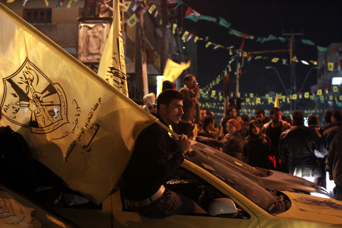 A Palestinian man holds a Fatah flag during celebrations marking the 48th anniversary of the Fatah movement in Gaza City, Thu