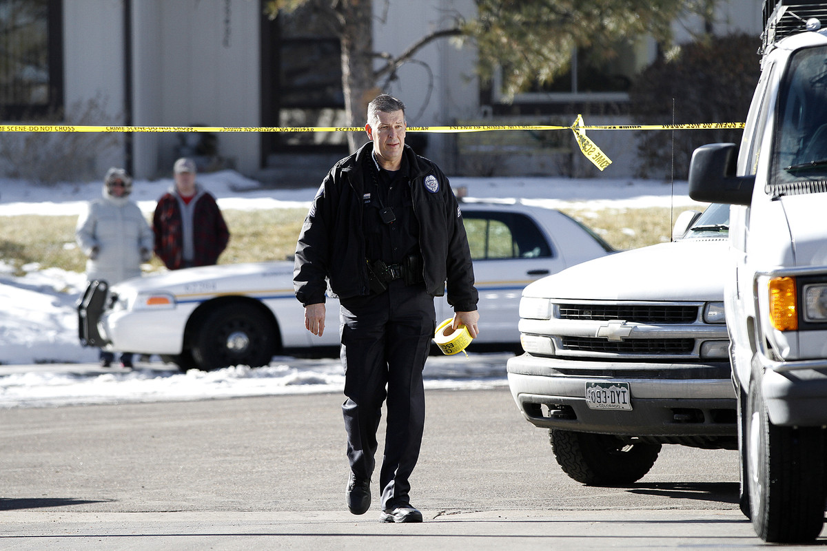AURORA, CO - JANUARY 5: An Aurora, Colorado police officer carries crime scene tape to close off the street in front of a tow