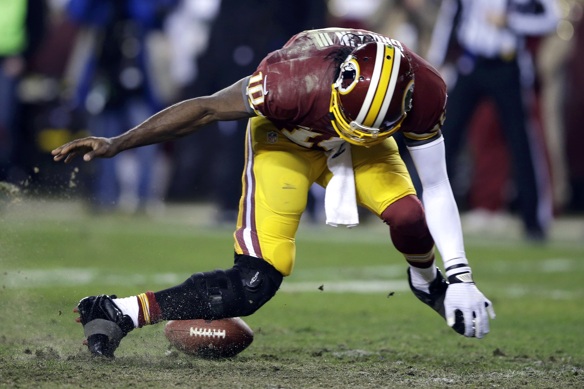 Washington Redskins quarterback Robert Griffin III twists his knees as he reaches for the loose ball after a low snap during