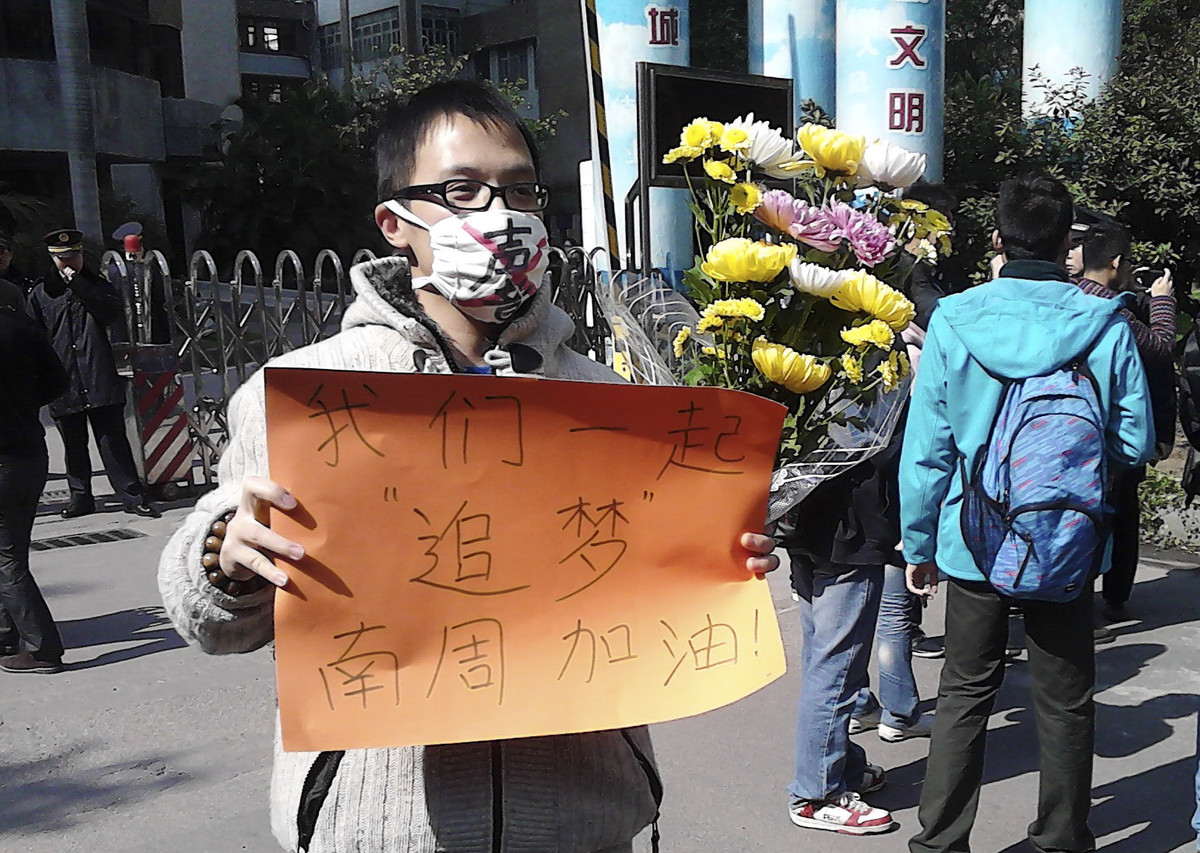 "In this photo taken and provided by activist Wu Wei, a man wearing a mask with words ""Silent"" holds a banner reading: ""Let's"