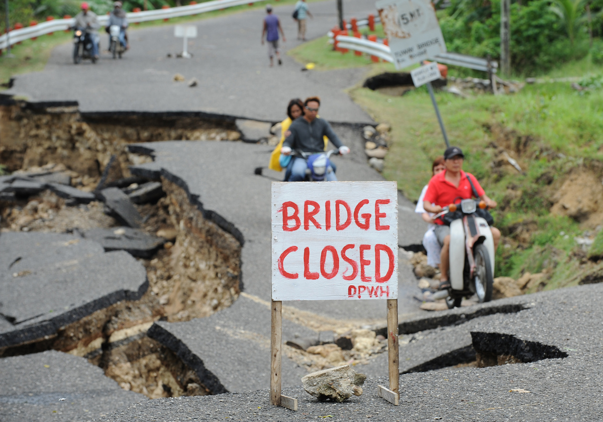 Motorists cross a damaged road destroyed at the height of the powerful earthquake in Guihulngan town, Negros Oriental provinc