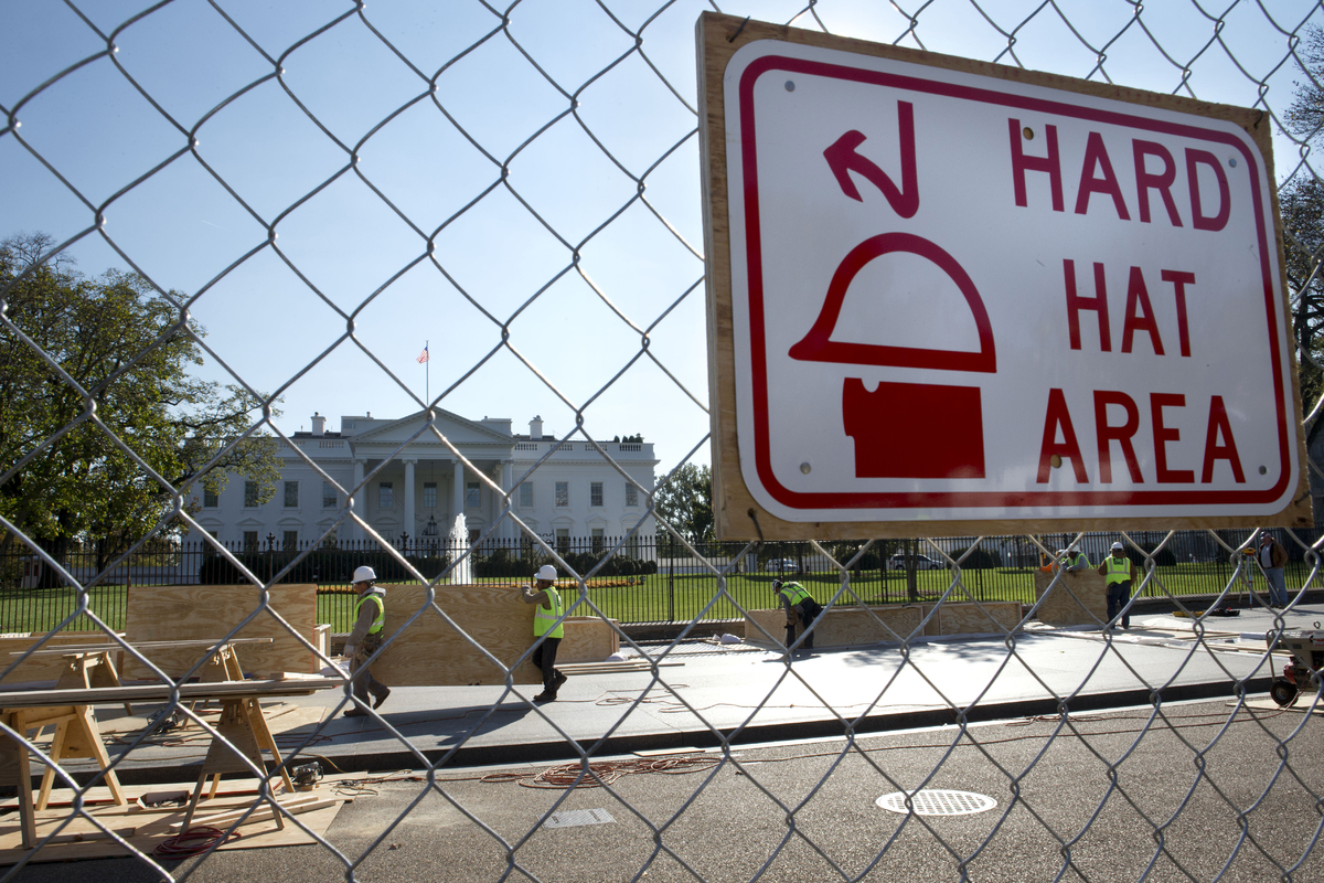 Behind a fence, workers with ABI Inc. work on inaugural stand construction in advance of the presidential inauguration, Monda