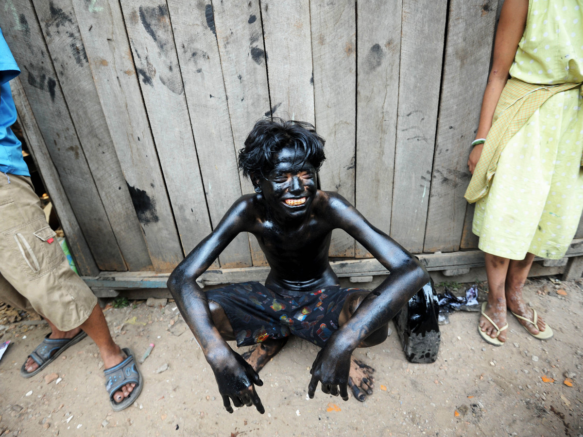 A Myanmar youngster (C) smeared with used car oil rests during a ball game using a coconut as part of celebrations to the 65t