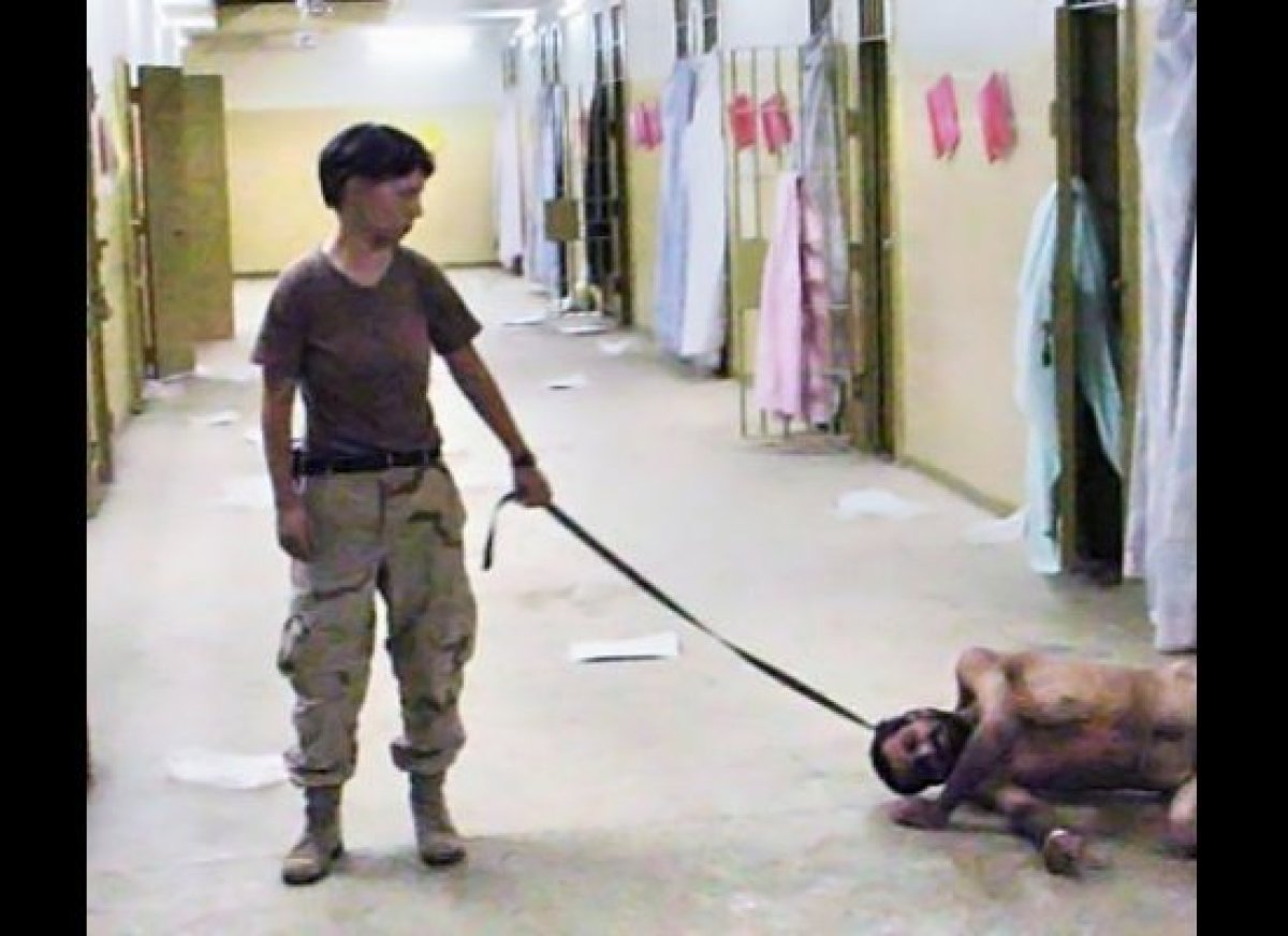 """United States Army photo from Abu Ghraib prison in Iraq showing Pvt. Lynndie England holding a leash attached to a prisoner"