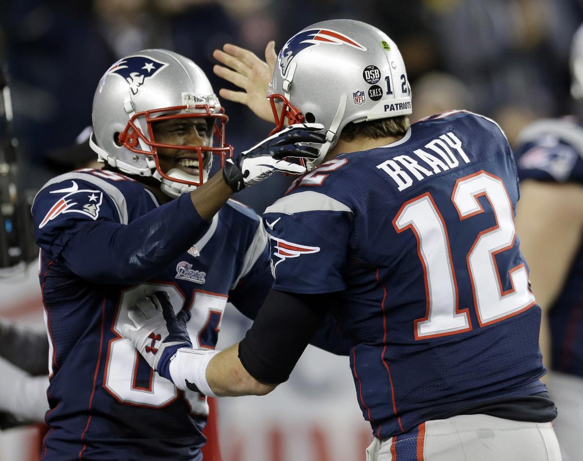 New England Patriots quarterback Tom Brady, right, congratulates teammate Brandon Lloyd after Loyd's five-yard touchdown pass
