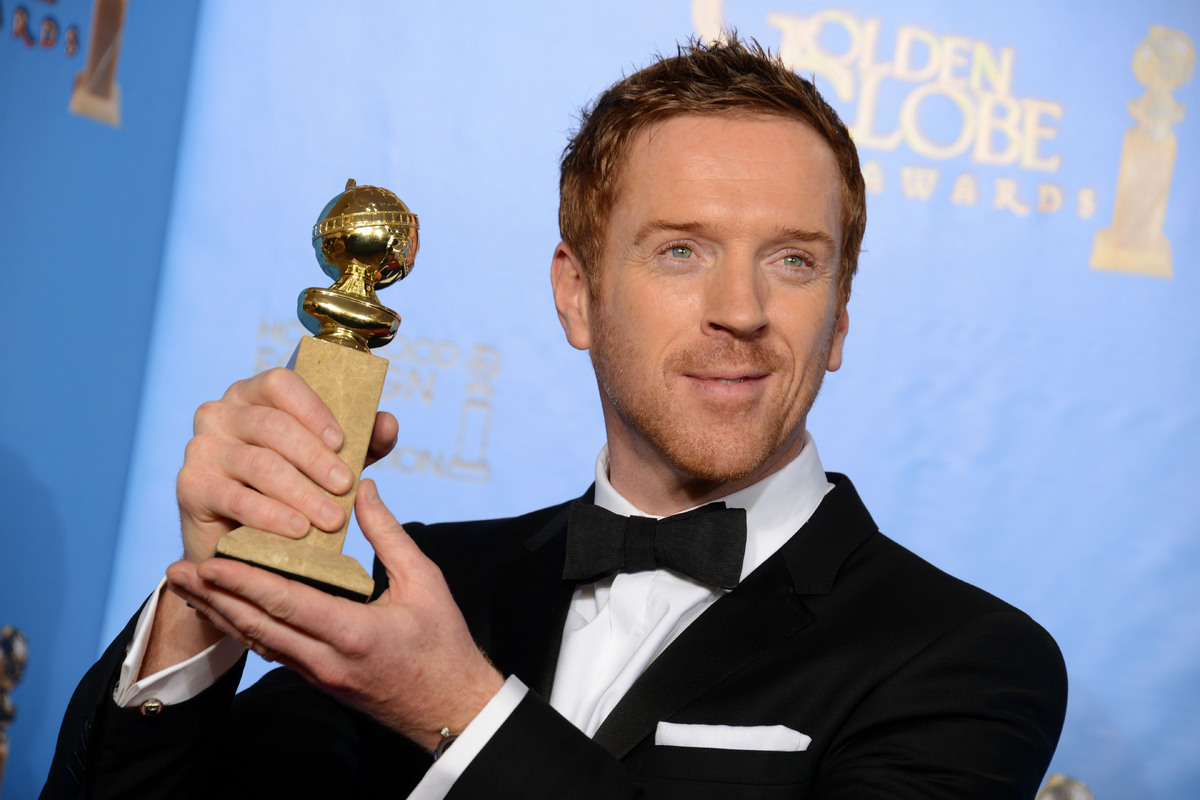 "Damian Lewis poses with the award for best performance by an actor in a television series – drama for ""Homeland"" backstage at"