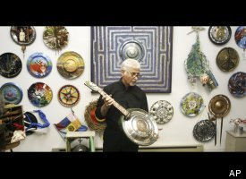 Ken Marquis, founder of the Landfillart Project, holds an art piece made into a six string musical instrument Tuesday, May 24