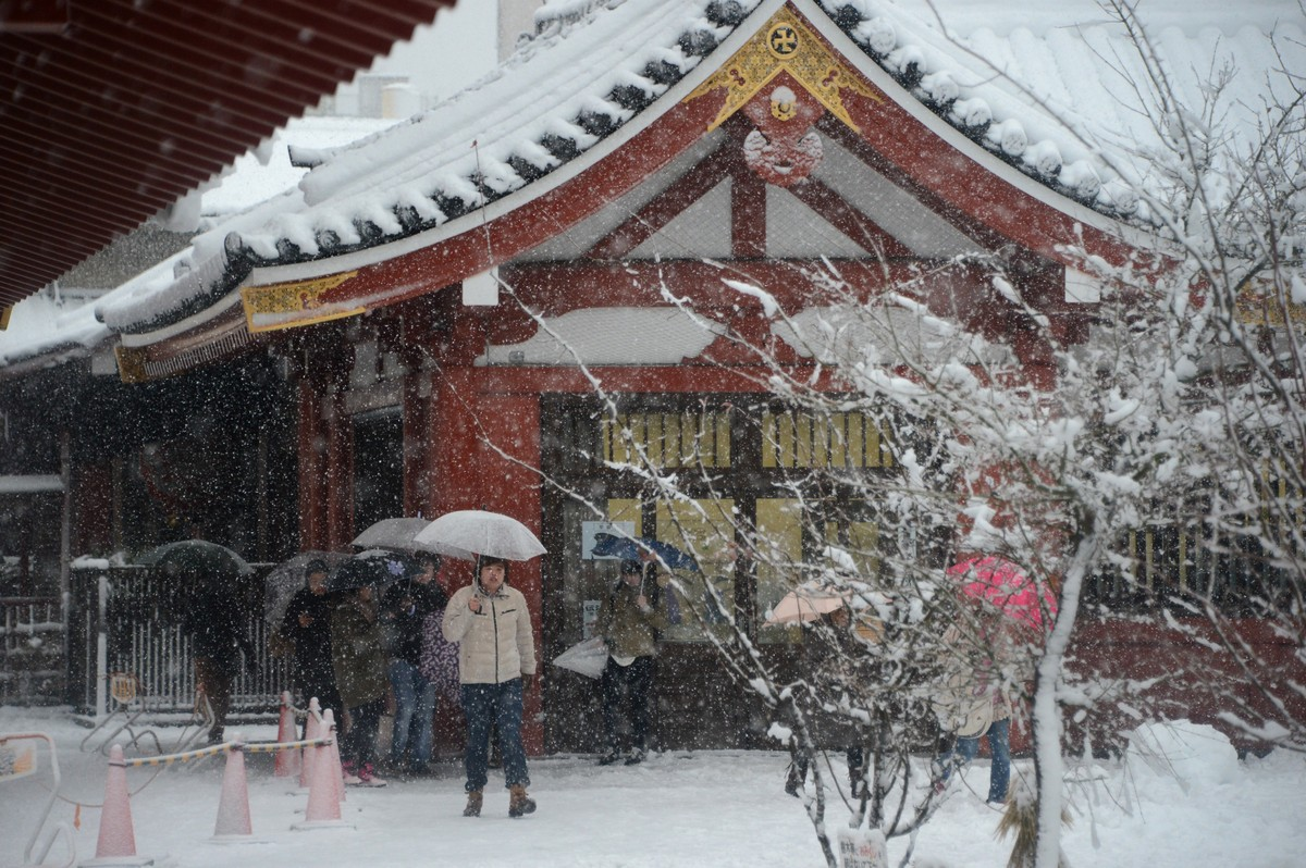 Visitors walk in the snow at Sensoji temple in the Asakusa area in Tokyo on January 14, 2013. A storm system grasped central