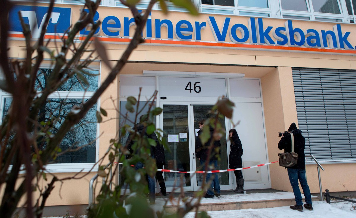 Customers and a camera man stand in front of a Berlin bank Monday Jan. 14, 2013. German police say a 30-meter (100-foot) tunn