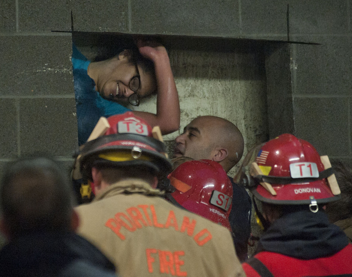 A woman is rescued from being trapped inside a wall of the parking garage at the Gretchen Kafoury Commons in SW Portland, Ore