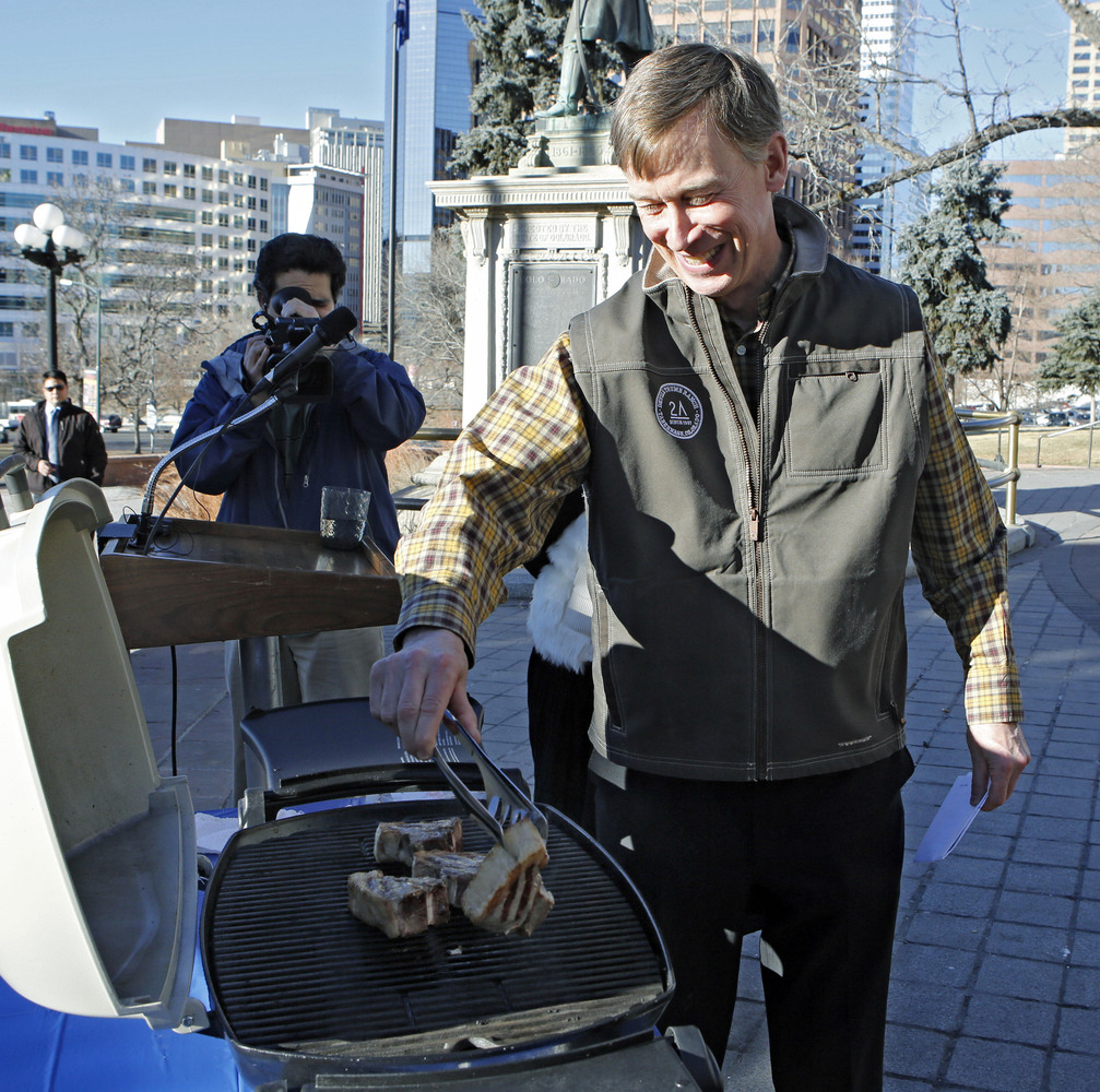 Colorado Gov. John Hickenlooper grill lamb chops to show Maryland Gov. Martin O'Malley how they are prepared, Thursday, Jan.