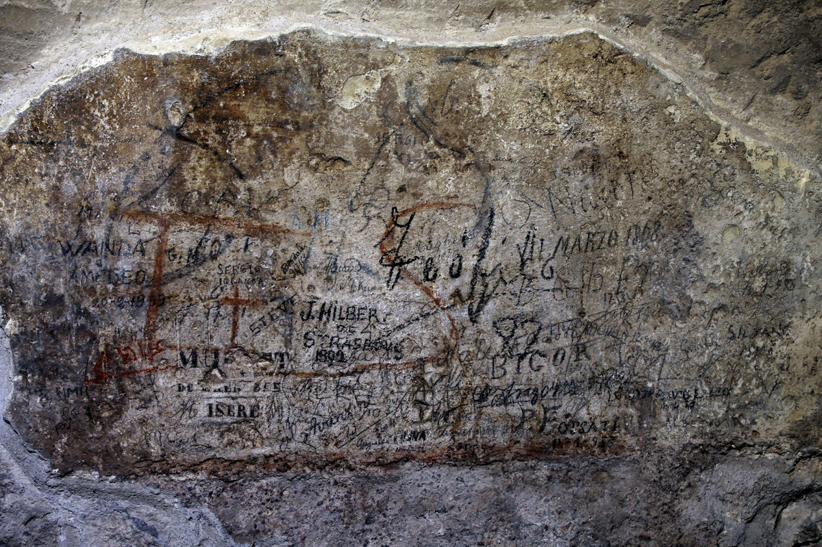 An ancient graffiti, in background red, covered by tourist's graffiti, is seen inside a gallery of Rome's Colosseum, Friday,