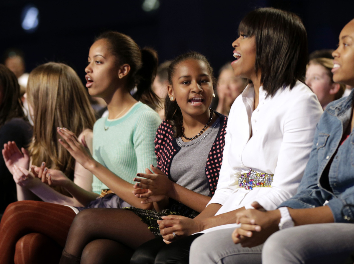 First lady Michelle Obama and daughters Sasha, center, and Malia react as Usher performs during the Kids' Inaugural: Our Chil