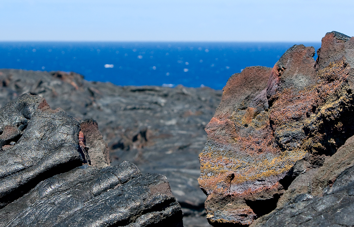 An aging lava flow looms out over the Pacific. During the day, the rocks are so hot it is unwise to touch them.