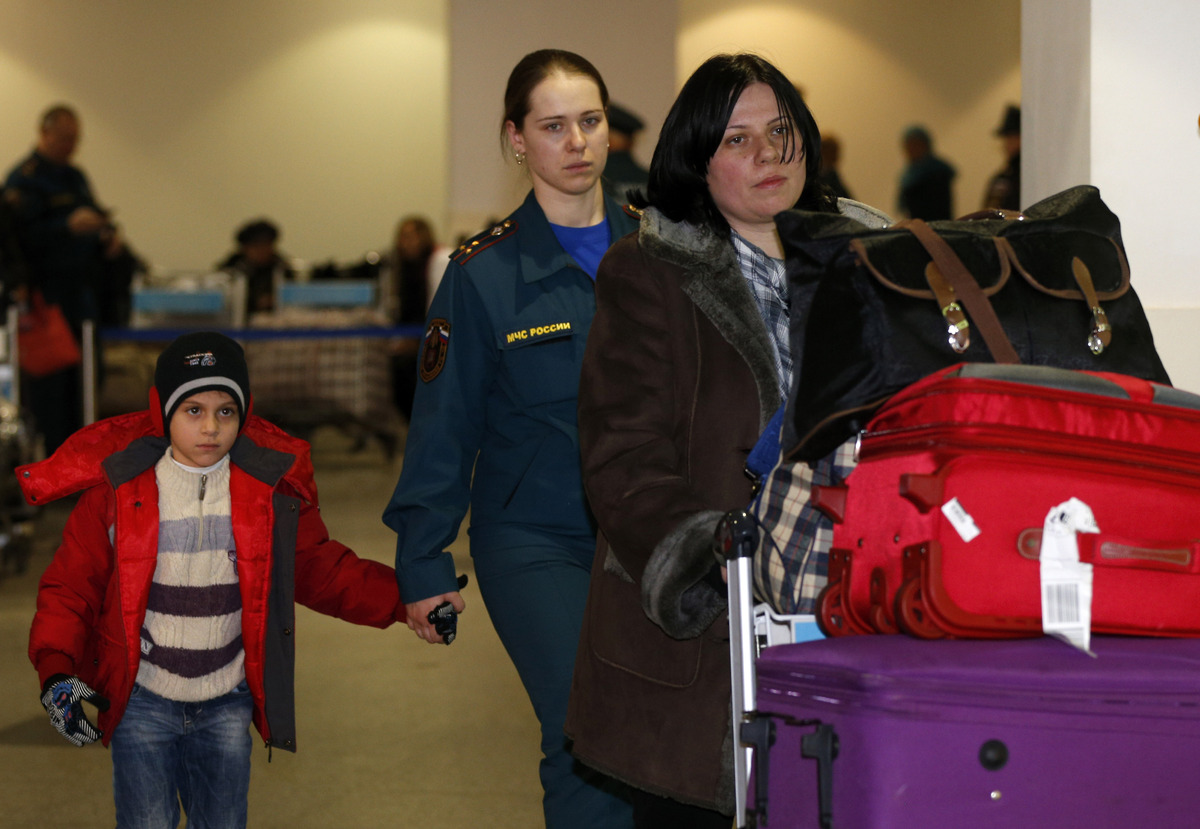 A Russian woman and her doughter, left, escorted by a Russian emergency situation officer, center, leave passport control zon