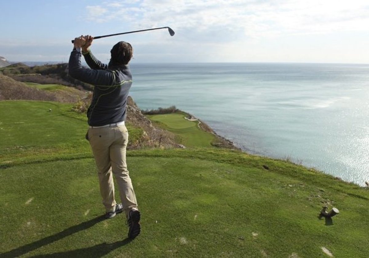 A player tees off from the cliff-top signature hole of the Thracian Cliffs Golf Course near Varna, Bulgaria. The Thracian Cli
