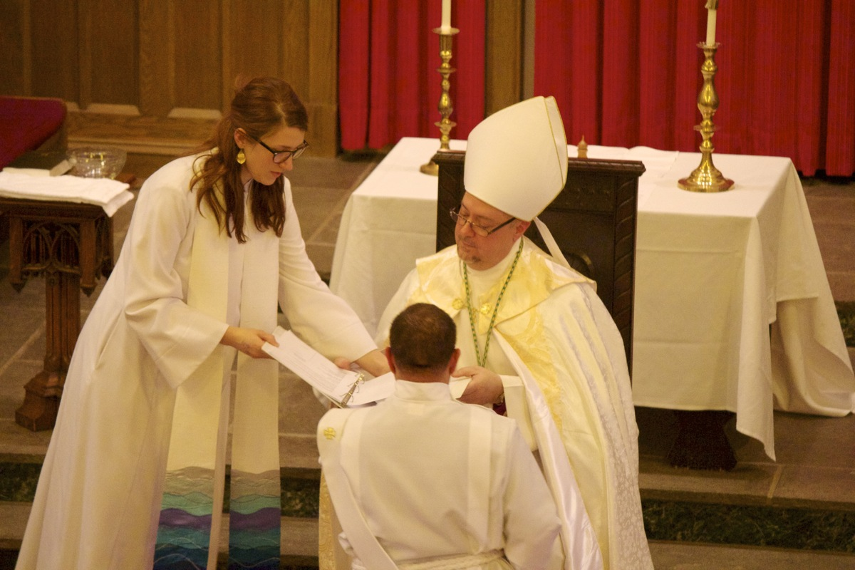 Bishop Benjamin Evan anoints the ordinand's hands with oil.