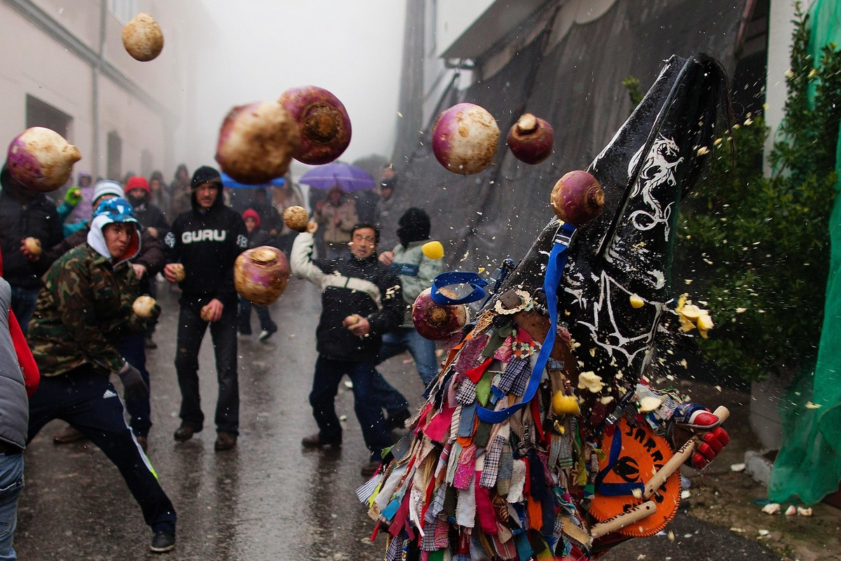 People throw turnips at the Jarramplas as he makes his way through the streets beating his drum during the Jarramplas Festiva