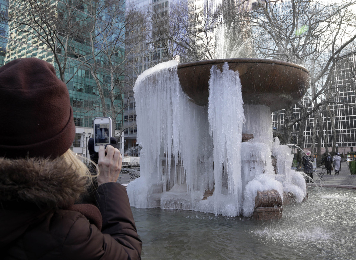 A woman pauses to take a photograph of the frozen fountain in New York's Bryant Park, in mid-town Manhattan, Thursday, Jan. 2