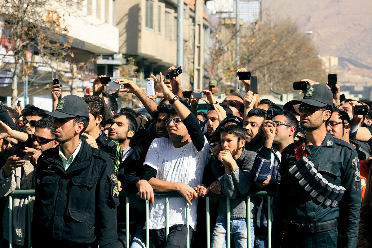 Iranians take photos with their mobile phones of authorities carrying out the court-ordered amputation of the fingers of a co